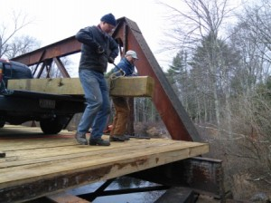 Denis and Mark maneuvering a large timber into place.