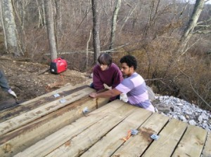 Becky and Josh rotating and positioning the last couple of decking timbers.