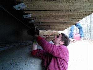 Wyatt ratcheting the lag screws with curved washers that hold the timbers in place.