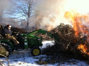 Harrison with his tractor pushing a burning pile.