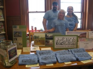 Dane, Ann and Harbour standing with the Wendemuth Meadow display at the North Brookfield May Festival