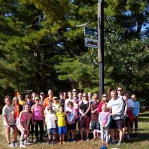 Runners posing by the Mass Central Rail Trail sign after the races were finished.